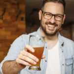 Guy smiling and holding glass of beer